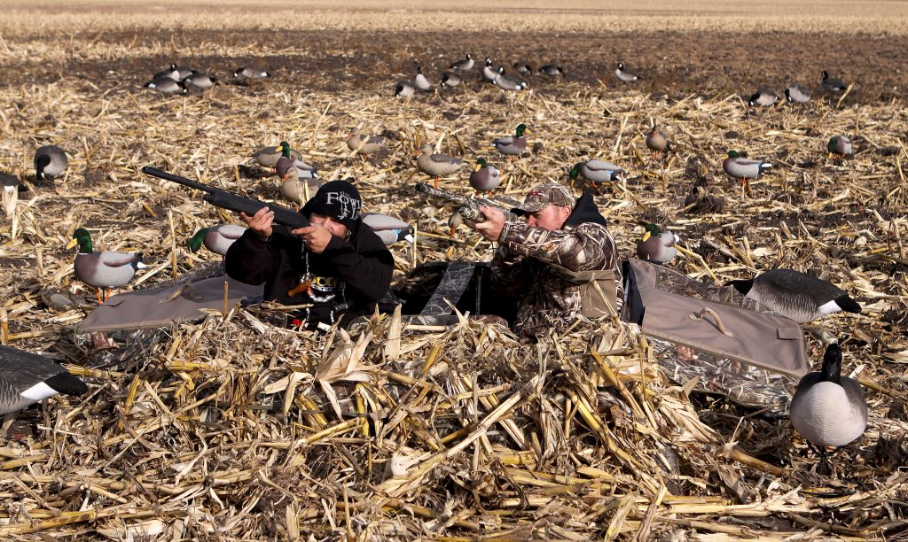 Photo of two hunters in layout blind.