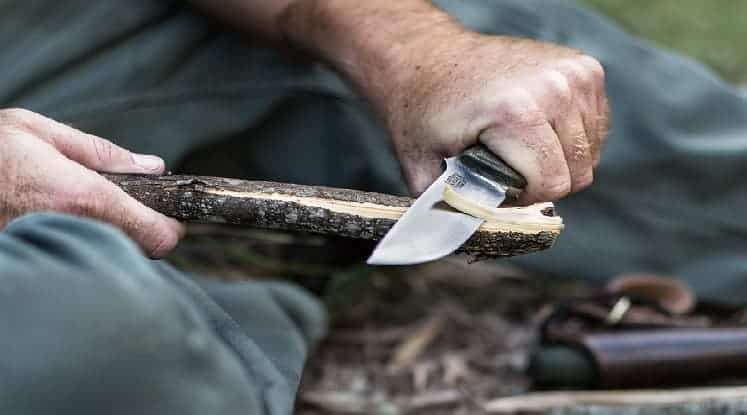 survival knife cuts wood