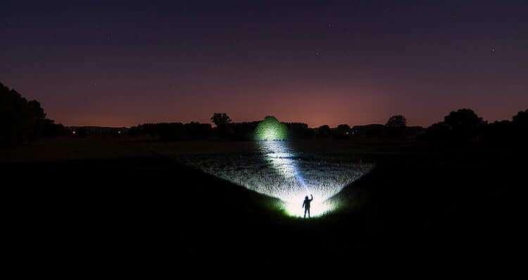man shines a flashlight away