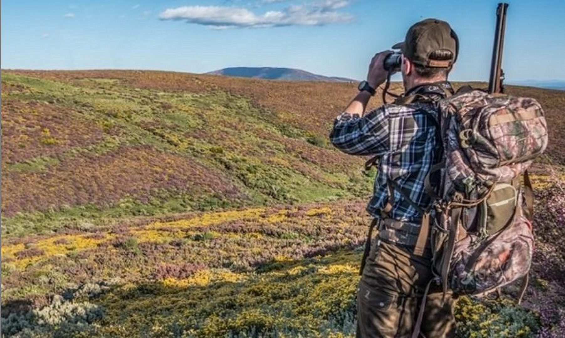 A hunter looks through binoculars 6 Awesome DayPacks for Hunting to Carry Everything You Need!