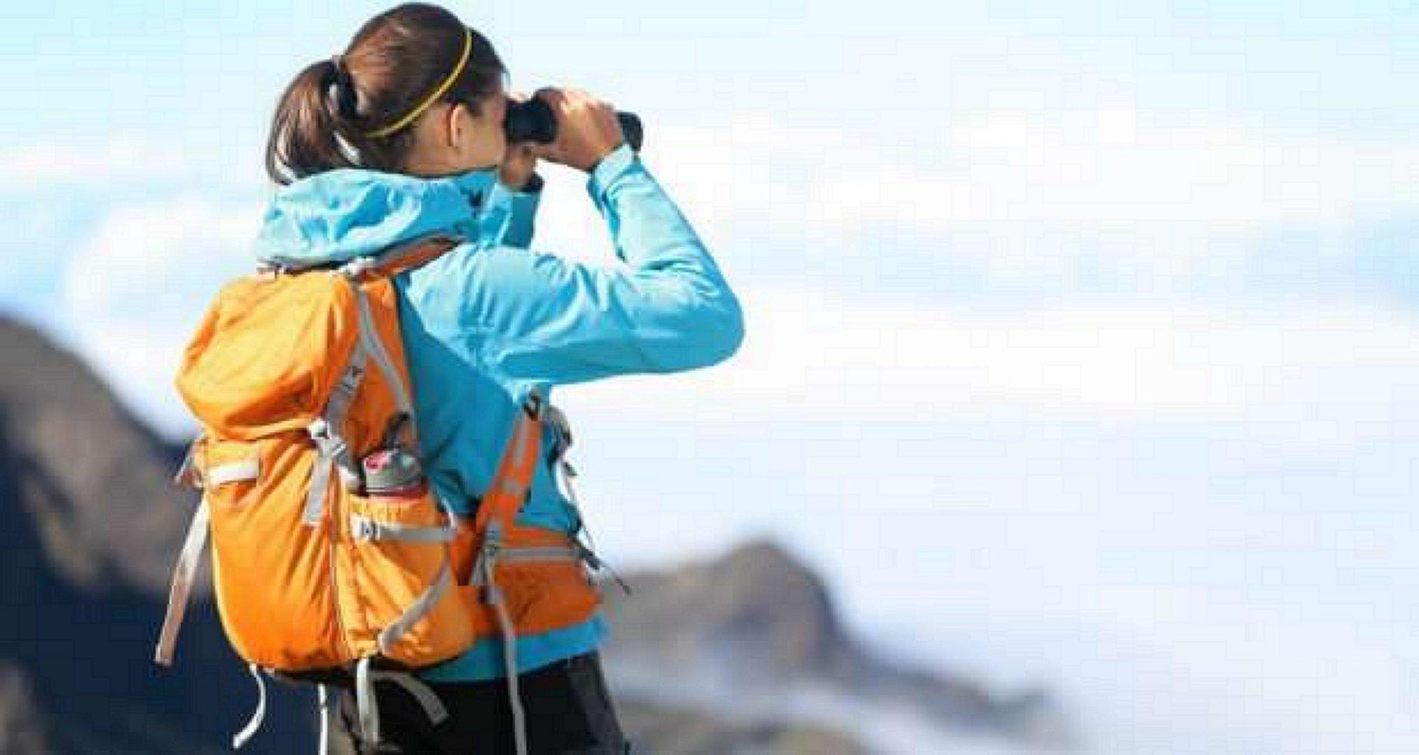 Girl in the mountains looks through binoculars