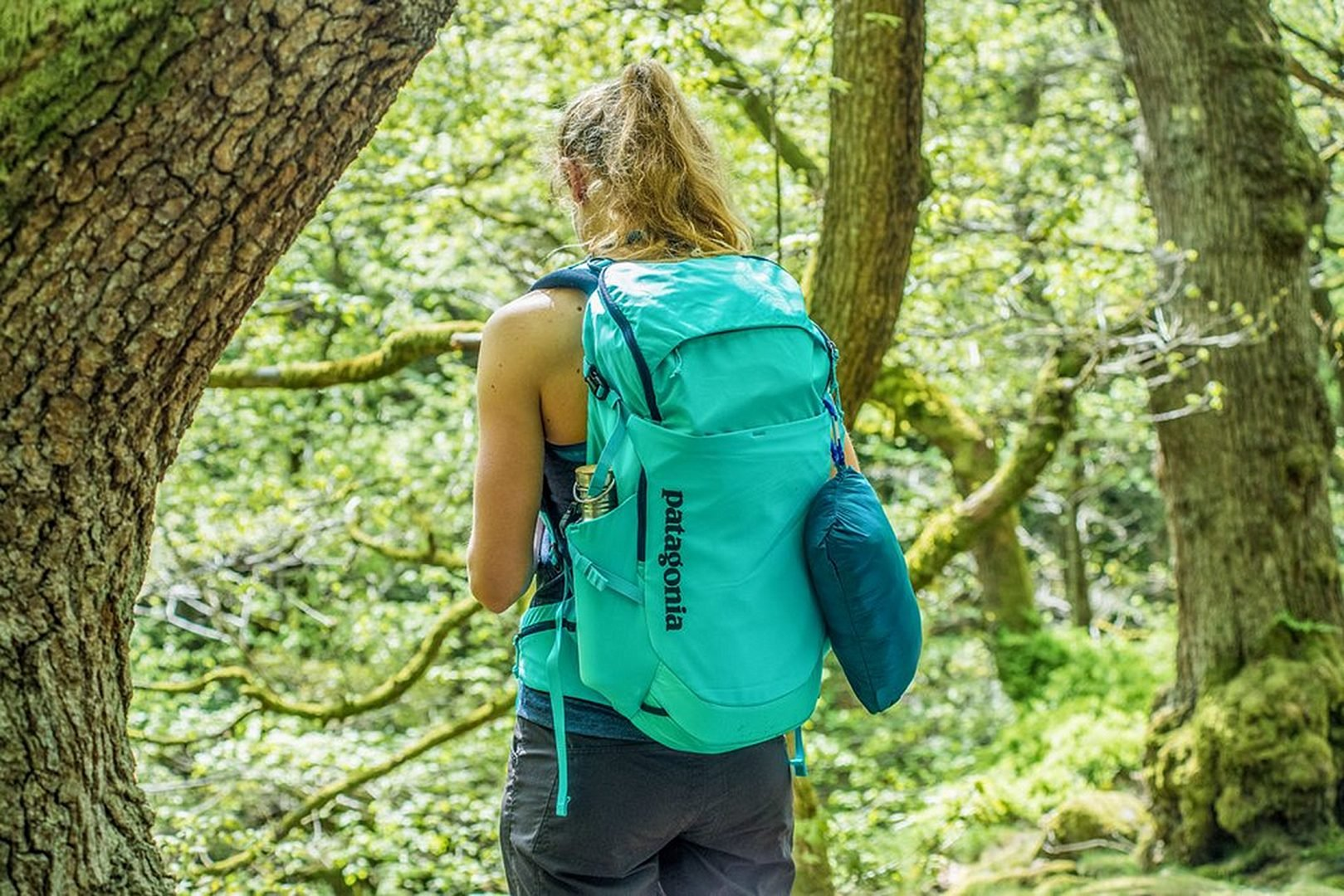 Woman carries the Patagonia Backpack Turqoise