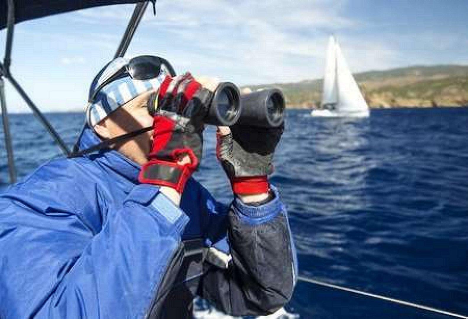 Man at the boat looks through binoculars