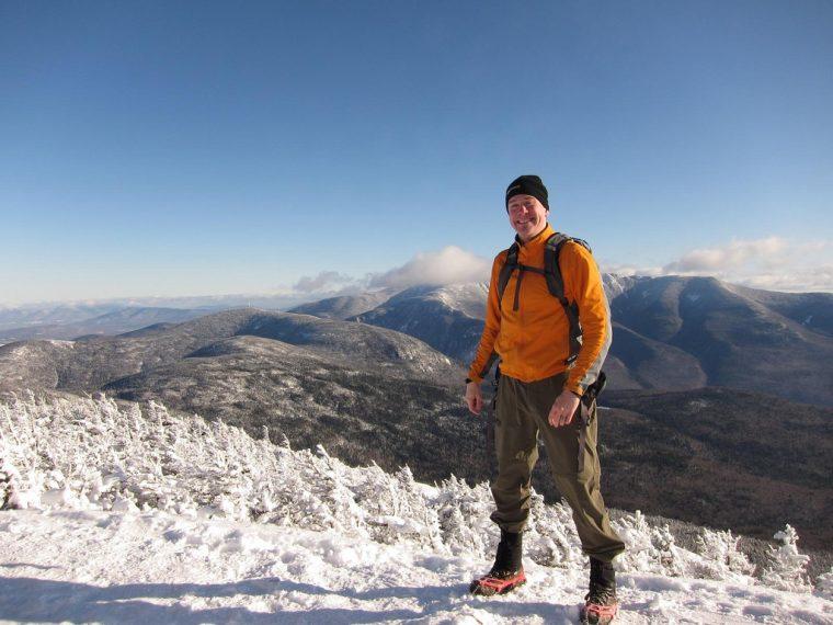 man hiking mountains snow