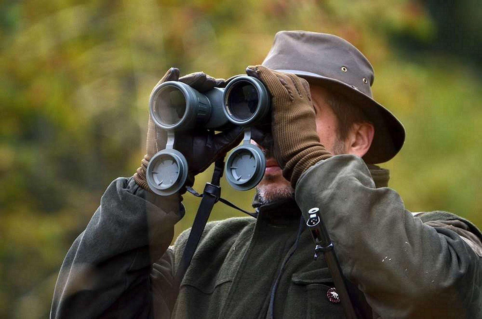 Man in a Hat looks through Binoculars