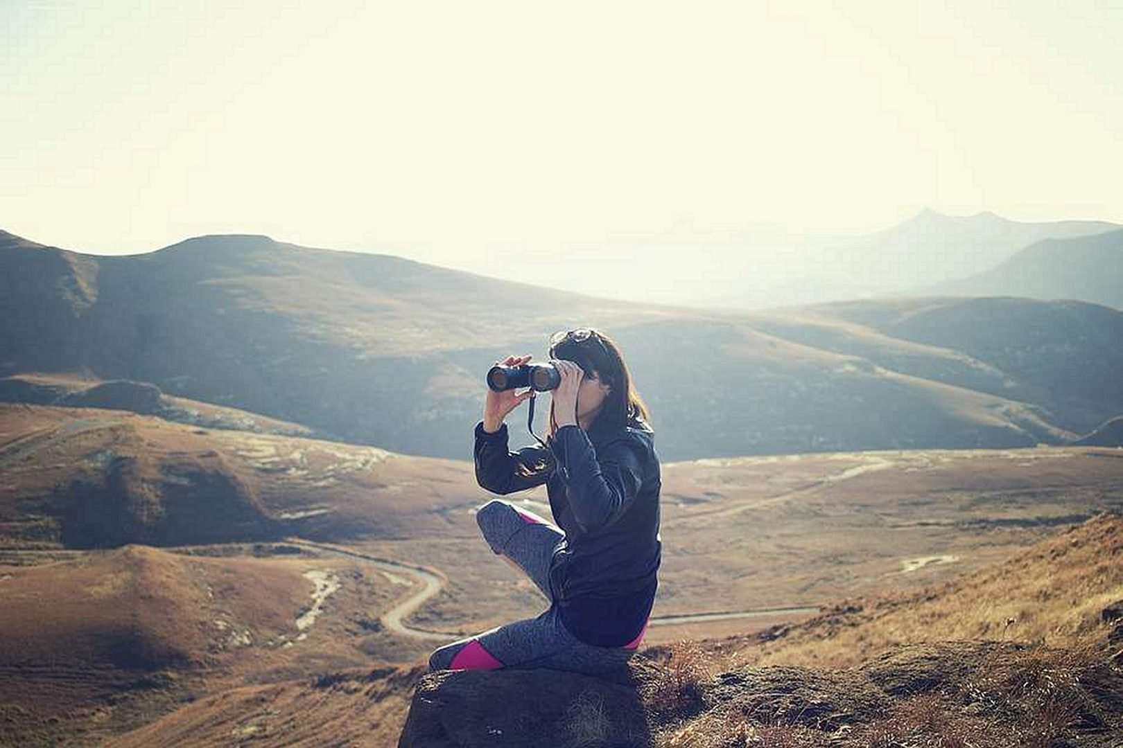 woman with binoculars in the mountains Best Budget Binoculars Under $100